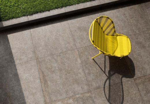 sedia gialla su pavimento esterno con grandi mattonelle in pietra naturale